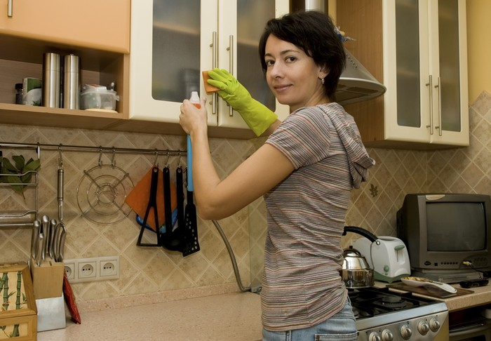 Женщина убирается на кухне