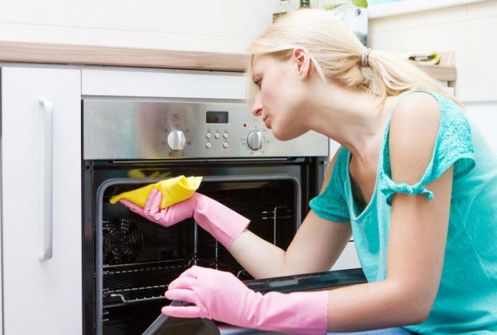 Девушка моет плиту