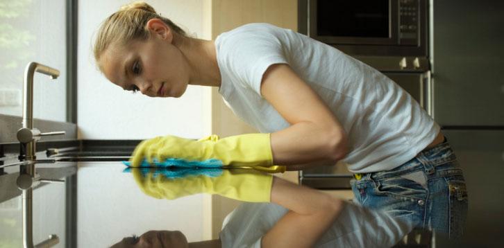 девушка убирается на кухне