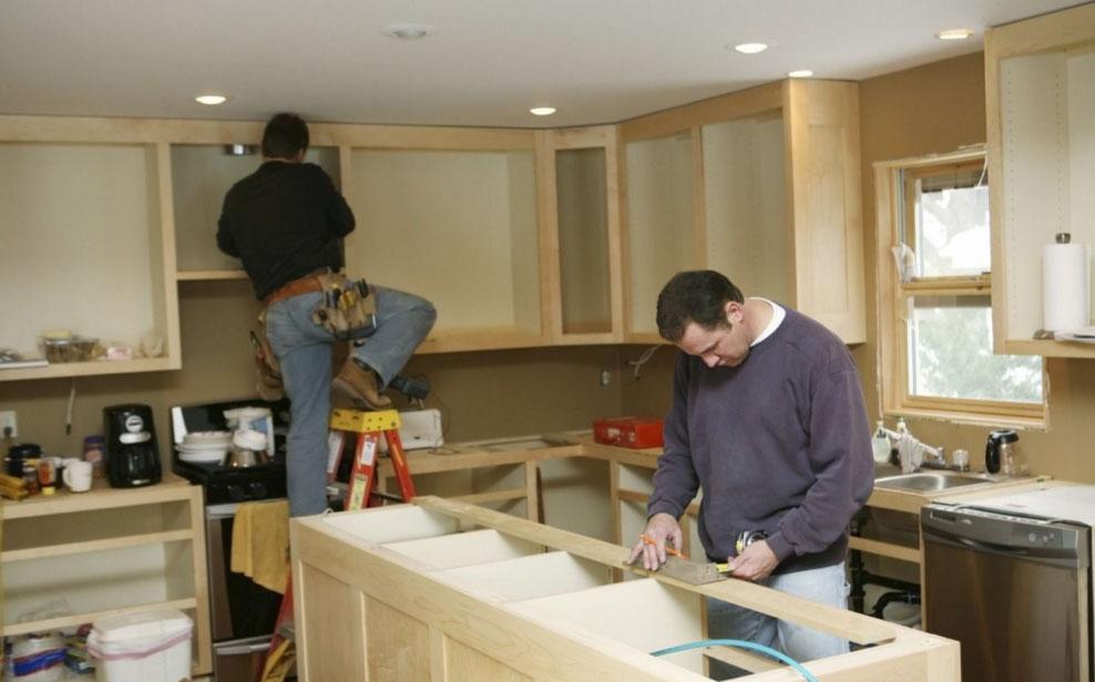 Специалисты собирают мебель на кухне
